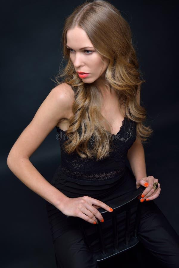 Bella donna in un vestito da sera nero che posa con la sedia fotografia stock libera da diritti