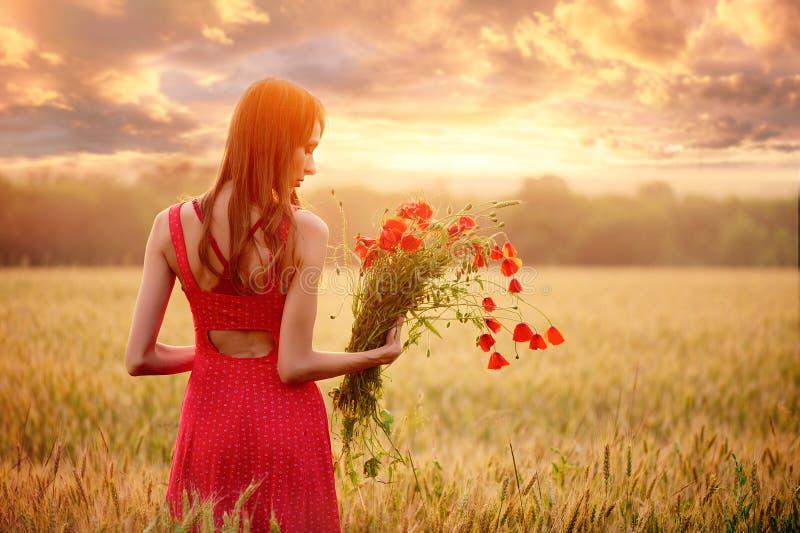 Bella donna in un vestito rosso con un mazzo dei papaveri in un giacimento di grano al tramonto, alla tonalità calda, alla felici fotografia stock