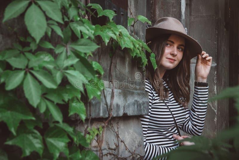 Bella donna in una camicia a strisce che tiene il suo cappello e che esamina una macchina fotografica fotografie stock libere da diritti