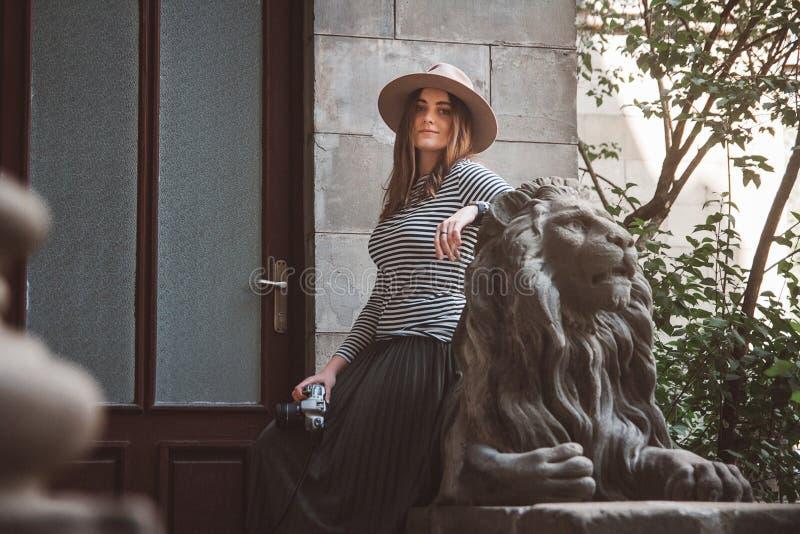 Bella donna in una camicia a strisce ed in un cappello Tiene la macchina fotografica vicino alla statua di un leone contro lo sfo fotografie stock