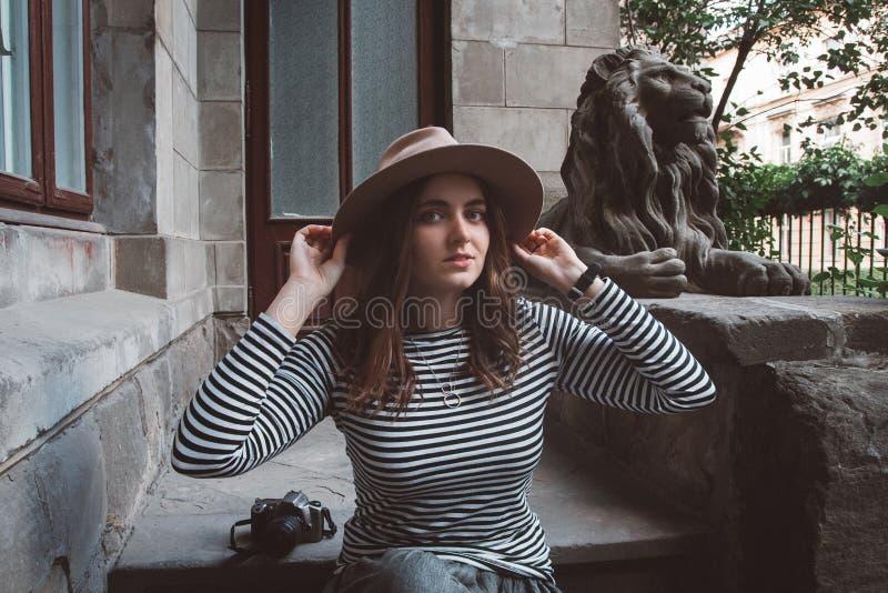 Bella donna in una camicia a strisce ed in un cappello Tiene la macchina fotografica vicino alla statua di un leone contro lo sfo fotografia stock libera da diritti
