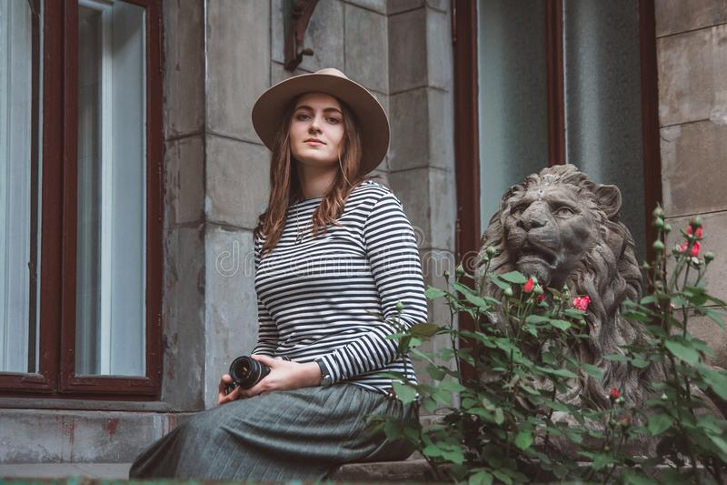 Bella donna in una camicia a strisce ed in un cappello Tiene la macchina fotografica vicino alla statua di un leone contro lo sfo fotografia stock