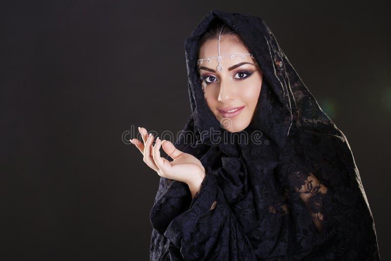 Bella donna in velo del Medio-Oriente di Niqab sulla b nera isolata fotografia stock