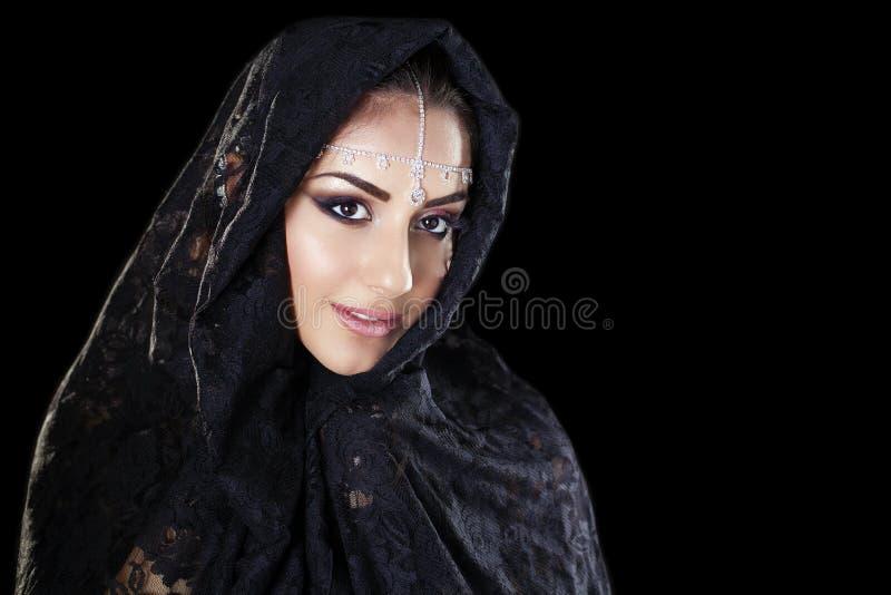 Bella donna in velo del Medio-Oriente di Niqab sulla b nera isolata immagini stock