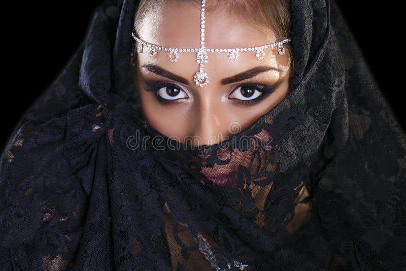 Bella donna in velo del Medio-Oriente di Niqab sulla b nera isolata fotografia stock libera da diritti