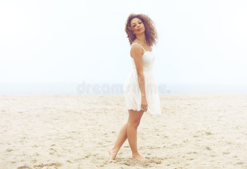 Bella donna in vestito bianco che cammina sulla sabbia alla spiaggia fotografia stock libera da diritti