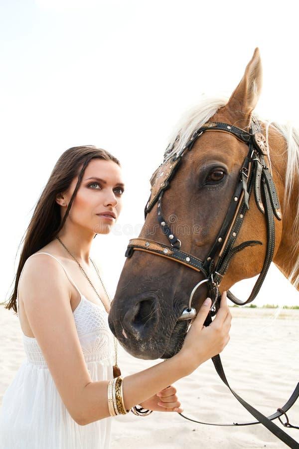 Bella donna in vestito bianco che posa con il cavallo contro il deserto immagini stock libere da diritti