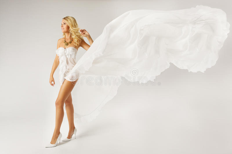 Bella donna in vestito bianco con il tessuto di volo fotografia stock libera da diritti