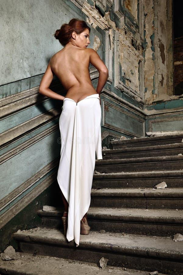 Bella donna in vestito bianco con la parte posteriore nuda in palazzo. fotografia stock libera da diritti