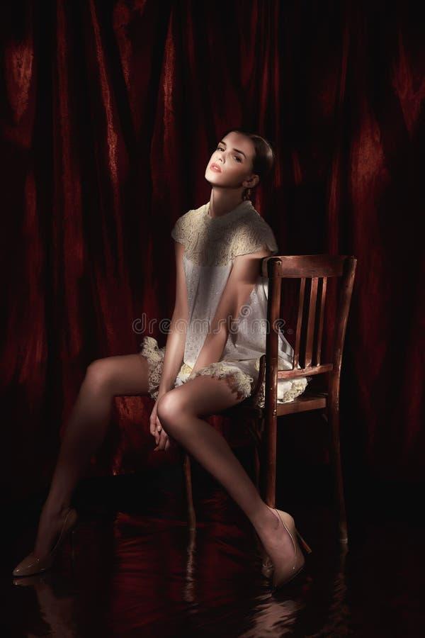 Bella donna in vestito bianco sul fondo scuro di Borgogna immagini stock