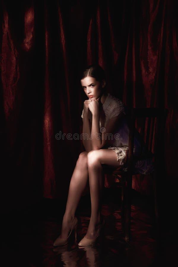 Bella donna in vestito bianco sul fondo scuro di Borgogna immagini stock libere da diritti