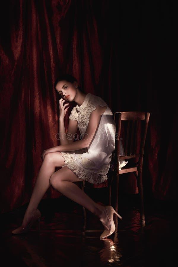 Bella donna in vestito bianco sul fondo scuro di Borgogna fotografia stock libera da diritti