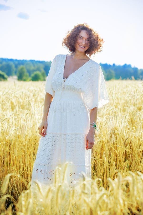 Bella donna in vestito bianco in un campo all'aperto su un'estate d fotografia stock libera da diritti