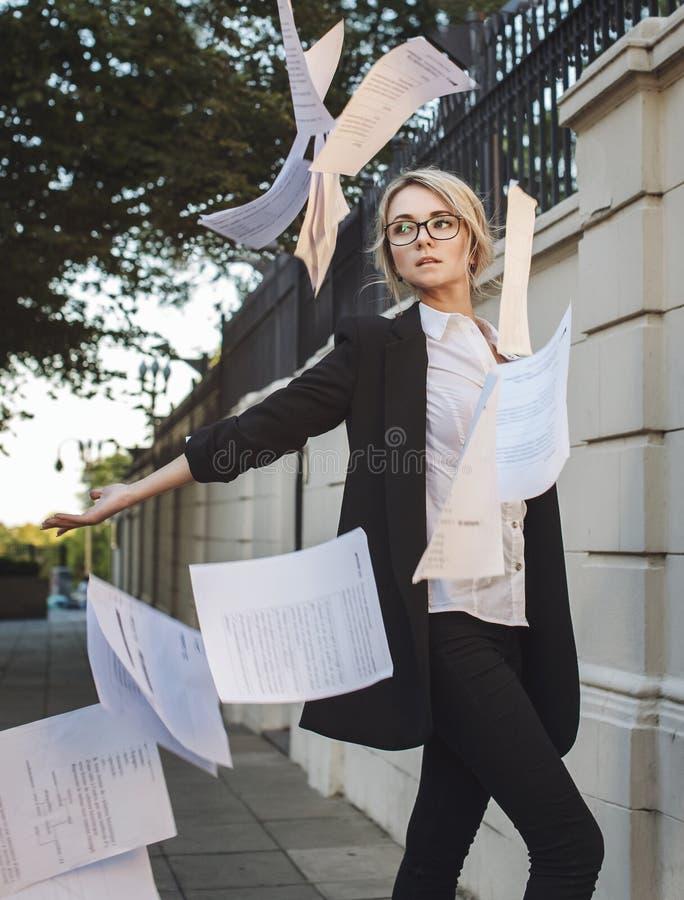 Bella donna in vestito classico occhiali che throuwing sulla p fotografie stock