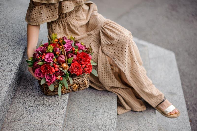 Bella donna in vestito lungo che si siede sulle scale concrete con il canestro di vimini dei fiori fotografia stock