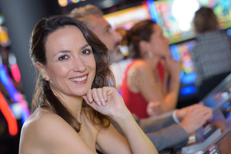 Bella donna in vestito rosso che gioca slot machine fotografie stock