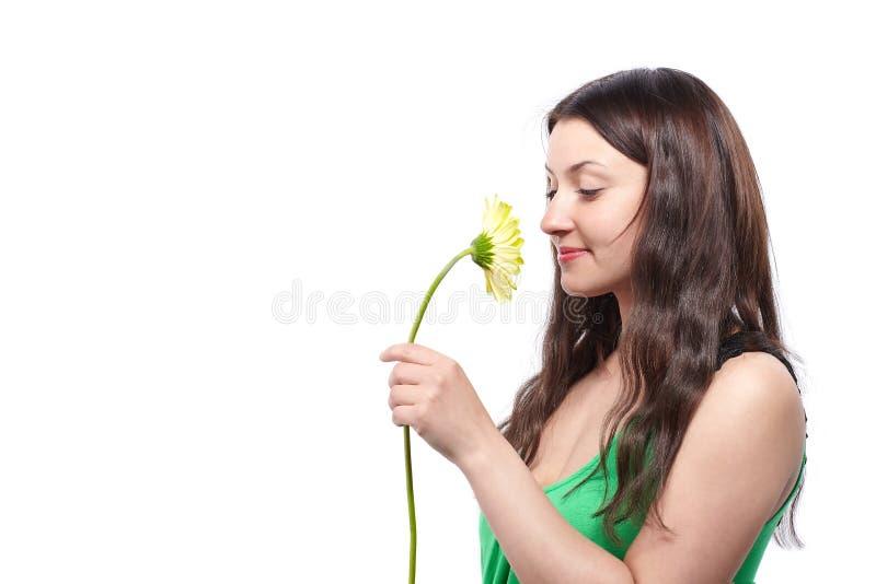 Bella donna in vestito verde che tiene un fiore giallo della gerbera a disposizione immagine stock