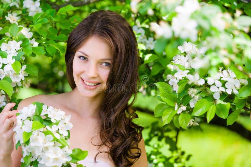 Bella donna vicino all'albero fiorito fotografie stock libere da diritti