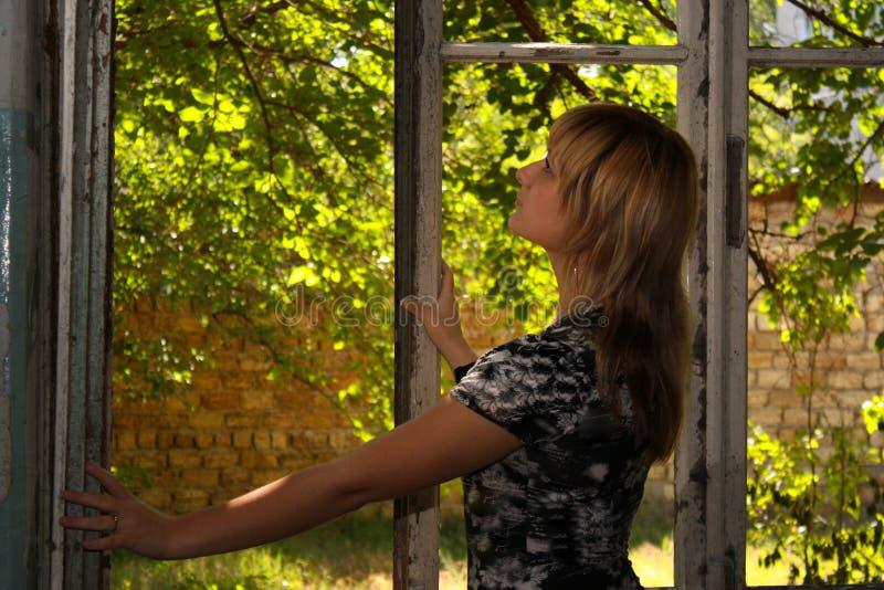 Bella donna vicino alle vecchie finestre fotografie stock