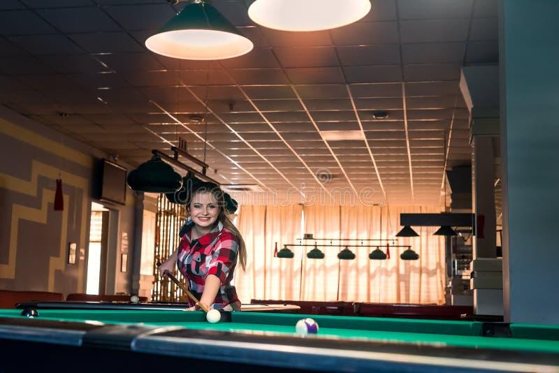 Bella e donna attraente in pub che gioca biliardo fotografia stock libera da diritti