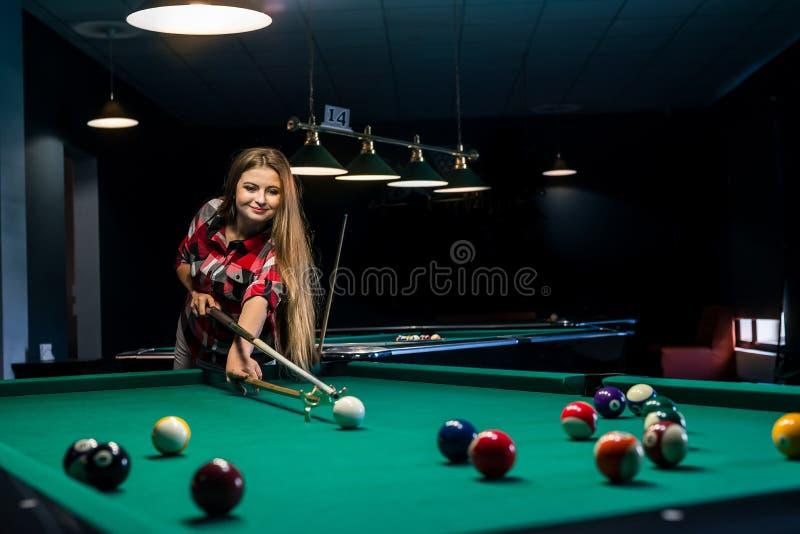 Bella e donna attraente in pub che gioca biliardo immagini stock