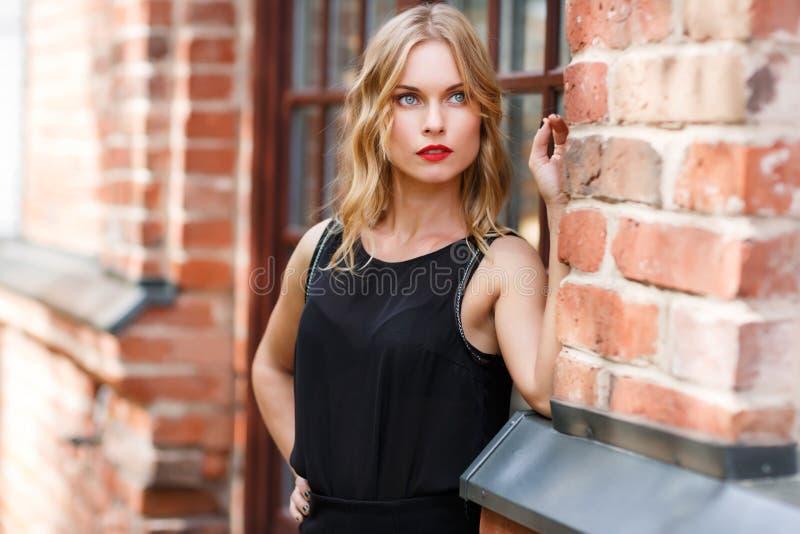 Bella e donna bionda alla moda che posa dopo con il muro di mattoni fotografia stock libera da diritti
