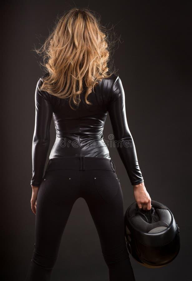 Bella e donna bionda sexy dalla parte posteriore, con il casco della bici del motore immagine stock libera da diritti