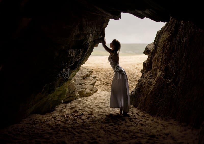 Bella e donna sexy in vestito, nei supporti e nelle pose lunghi in una caverna accanto ad una spiaggia sabbiosa in Irlanda fotografie stock libere da diritti