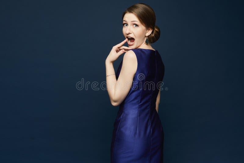 Bella e giovane donna castana alla moda in vestito blu isolato a fondo scuro fotografia stock libera da diritti