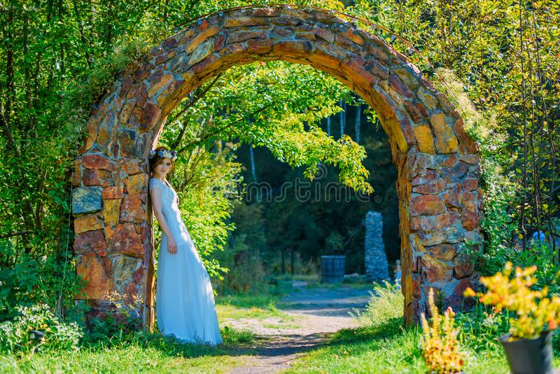 Bella e giovane sposa in vestito e cerchietto bianchi dei fiori che posano nell'arco di pietra immagine stock libera da diritti