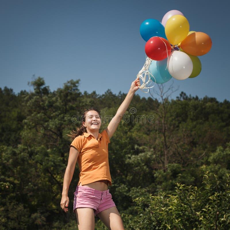 Bella e ragazza atletica che salta con i palloni fotografie stock