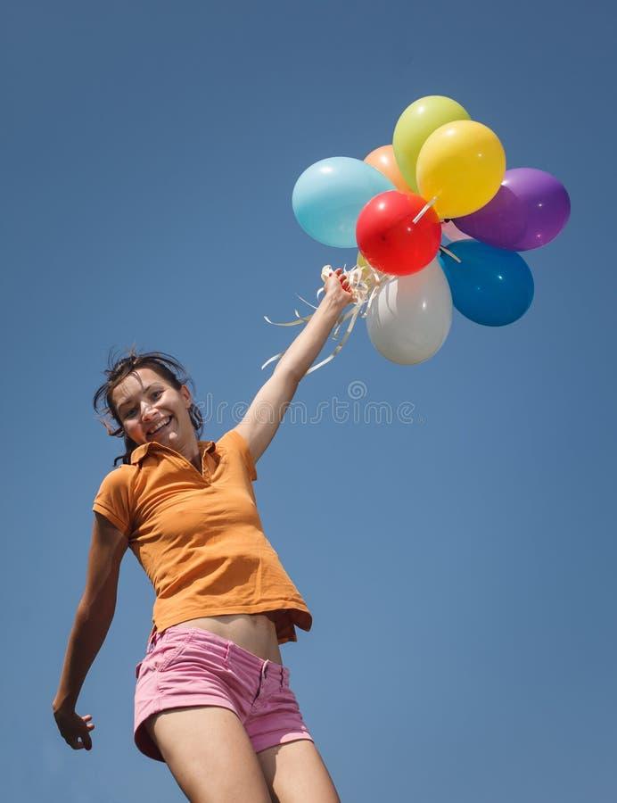 Bella e ragazza atletica che salta con i palloni fotografia stock