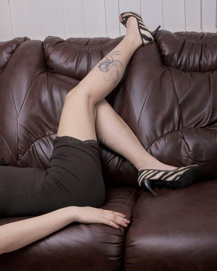 Bella e ragazza attraente sul sofà fotografia stock