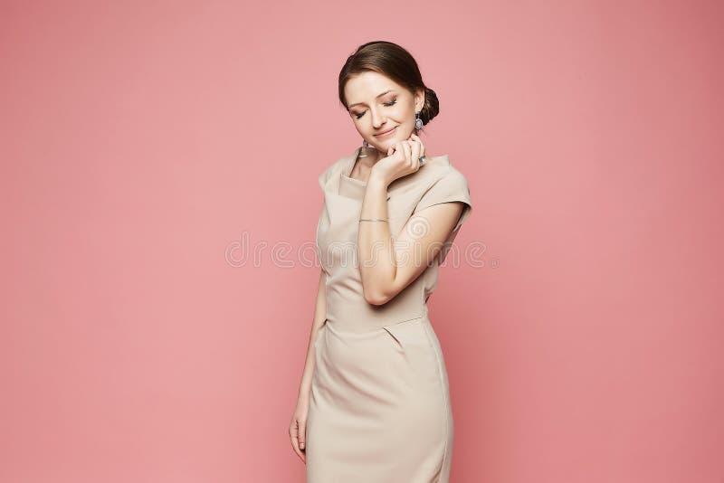 Bella e ragazza di modello castana alla moda allegra con trucco luminoso, in vestito beige e con gli orecchini sorridente e posan immagini stock libere da diritti