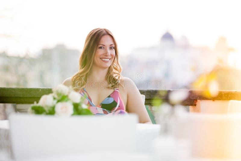 Bella e seduta sorridente incantante della donna all'aperto fotografia stock