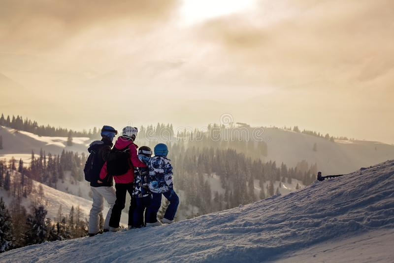 Bella famiglia con i bambini, scianti in un'area di paesaggio in austriaco fotografie stock