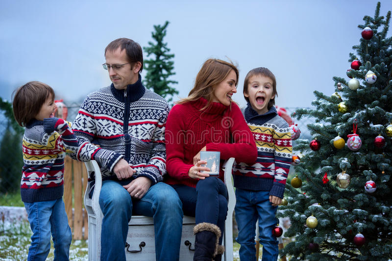 Bella famiglia di quattro felice, divertendosi all'aperto nella neve fotografia stock libera da diritti