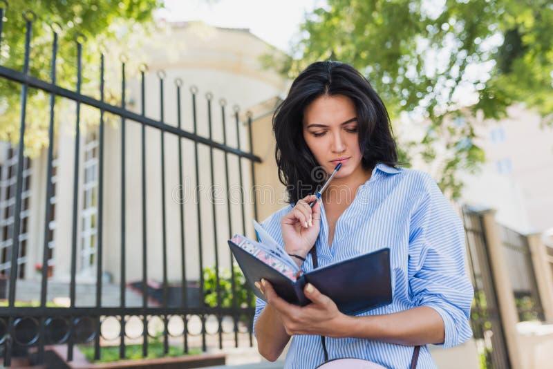 Bella femmina castana europea seria che porta camicia blu, facente le note in taccuino mentre camminando all'aperto su una via de immagini stock libere da diritti