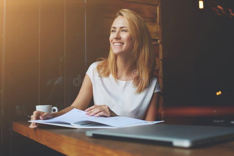 Bella femmina con il sorriso sveglio che distoglie lo sguardo mentre rilassandosi dopo il lavoro sul suo computer portatile immagini stock libere da diritti
