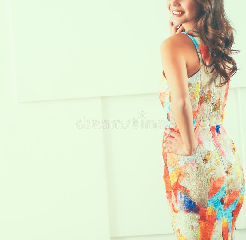 Bella femmina in prendisole che posano sul fondo bianco immagine stock
