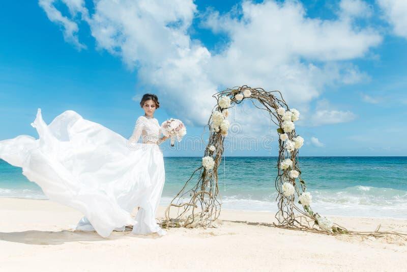 Bella fidanzata castana in vestito da sposa bianco con grande lungo fotografia stock libera da diritti