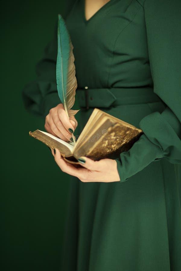 Bella figura della donna in libro verde scuro dell'annata della tenuta del vestito da 50 ` s immagini stock libere da diritti