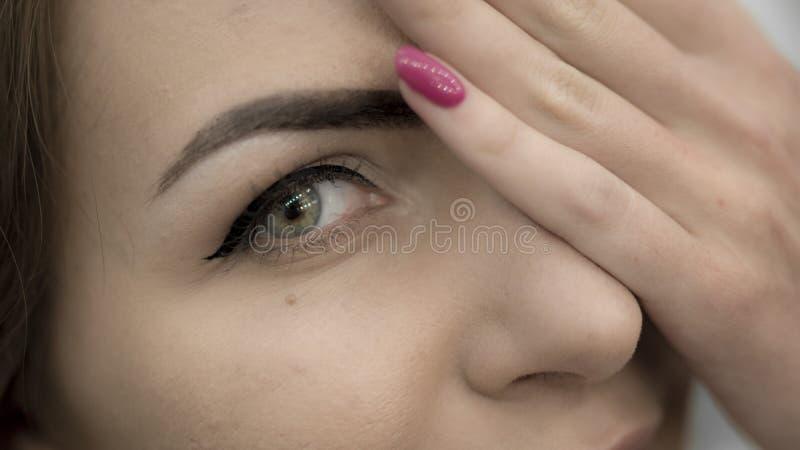 Bella fine dagli occhi verdi della donna una metà del suo fronte con la mano fotografia stock libera da diritti