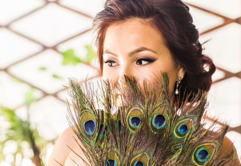 Bella fine della donna su con il fan fatto della piuma del pavone immagini stock