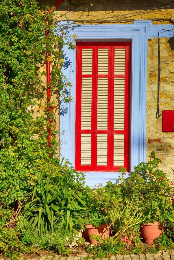 Bella finestra blu e rossa nella casa mediterranea del villaggio immagini stock