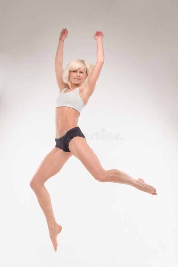 Bella giovane bionda in un salto fotografia stock