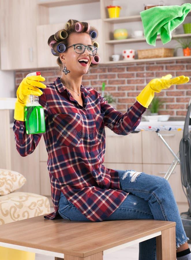 Bella giovane casalinga con il bigodino che fa i lavoretti della casa fotografie stock libere da diritti