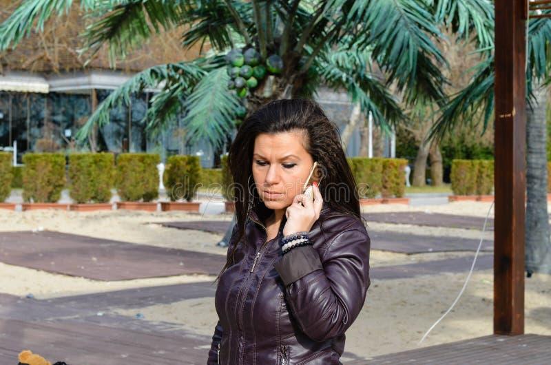 Bella giovane conversazione castana arrabbiata sul telefono fotografia stock libera da diritti