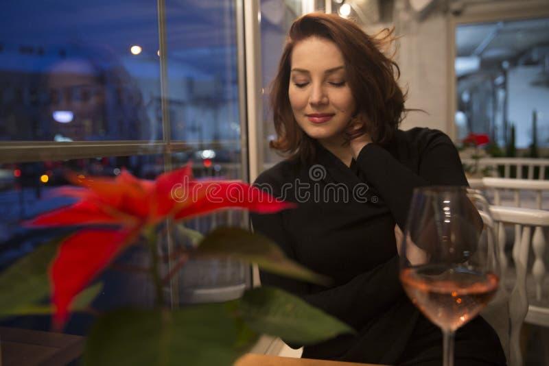 Bella giovane donna ad una tavola vicino alla finestra in un resta accogliente fotografia stock libera da diritti