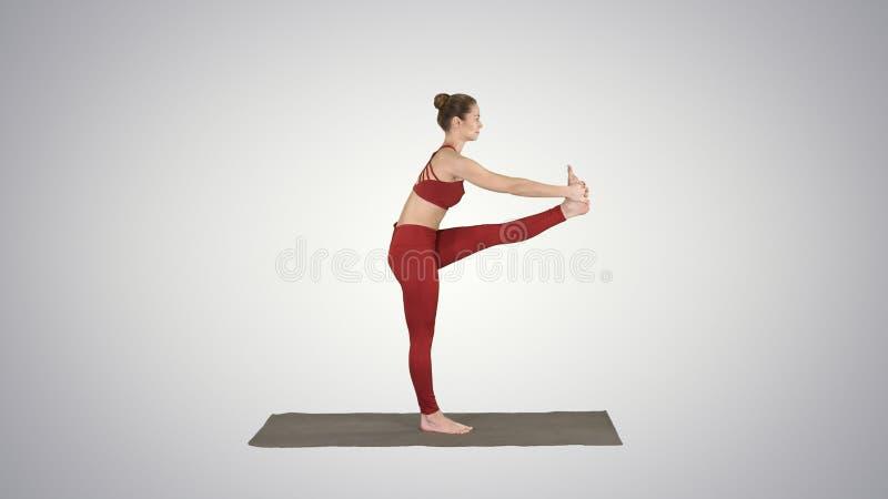 Bella giovane donna adatta in abiti sportivi che fanno esercizio di sport, piegante nella variazione di Utthita Hasta Padangustha fotografie stock